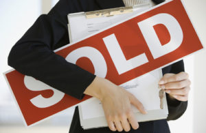 Woman holding Sold Sign